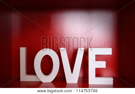 Word LOVE on red background, close up