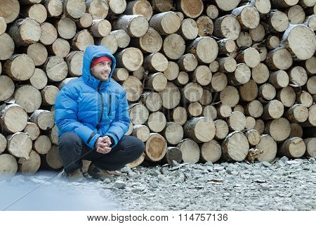 Squatting lumberjack at stack of logged firewood background outdoors in winter mountain forest