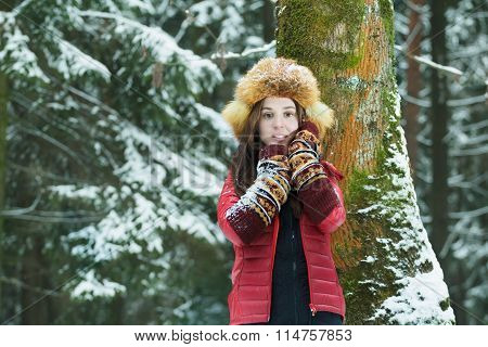 Winter outdoor portrait of student brunette girl wearing red down sweater and scarlet fur ushanka ha