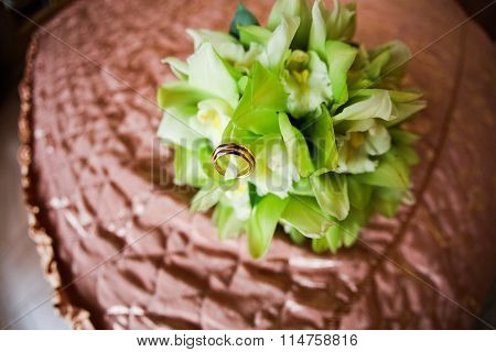 Wedding Rings On Wedding Bouquet And A Green Bed