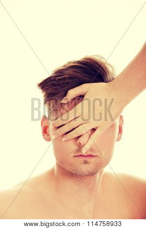 Woman's hand covering man's eyes.