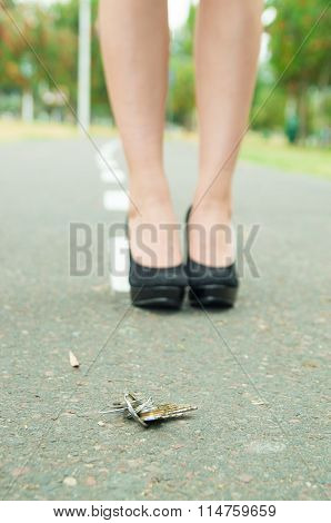 Keys lying on asfalt surface and elegant woman feet wearing high heels standing behind, visible from
