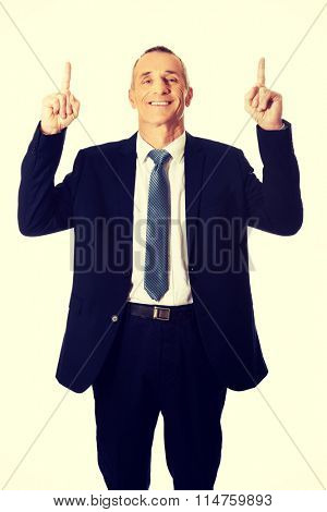 Businessman pointing upwards