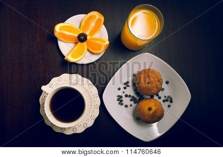 Elegant breakfast concept seen from above, coffee cup, choc chip muffin, orange juice and sliced ora