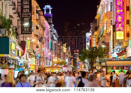 XIAMEN, CHINA - JUNE 11, 2014: Pedestrians walk on Zhongshan Road at night. The road is the main commercial street in Xiamen and parts have been fully pedestrianized.