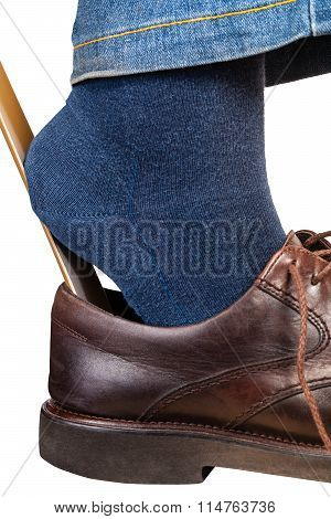 Man Puts On Brown Shoes Using Shoe Horn Close Up