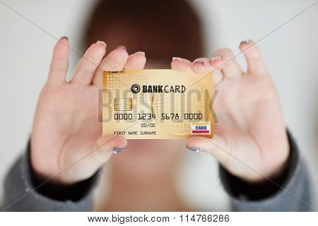 A beautiful woman holds out a business or credit card