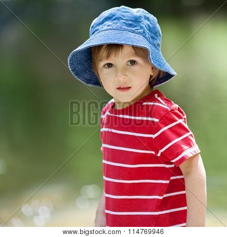 Portrait Of A Cute Boy With Summer Hat On A Edge Of A River