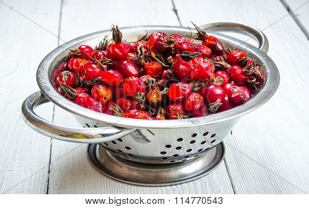Rosehips In Metal Bowl On Wooden Table.