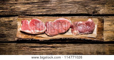 Medallions Of Raw Meat On The Bark Of A Tree.