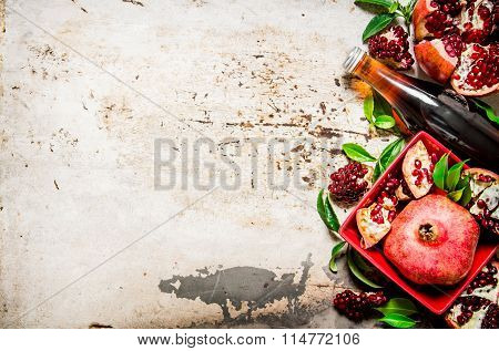 Pomegranate Juice In A Bottle And Pieces Of Pomegranate With Leaves.