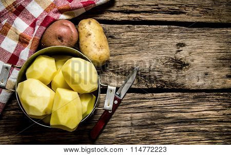 Peeled Potatoes In An Old Pan With Knife On Wooden Table . Free Space For Text.