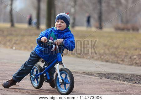 little boy riding runbike, early sport