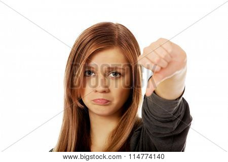 Young unhappy teenage woman showing thumb down