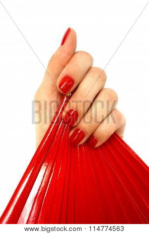 Red fan in hand with red manicure on white background