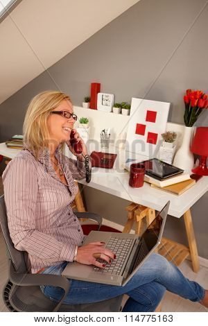 Happy young blonde woman sitting in chair at home, holding laptop computer on lap talking on phone, smiling. Side view.