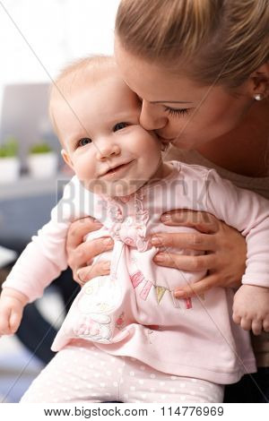 Closeup photo of mother holding and kissing tender little baby daughter.