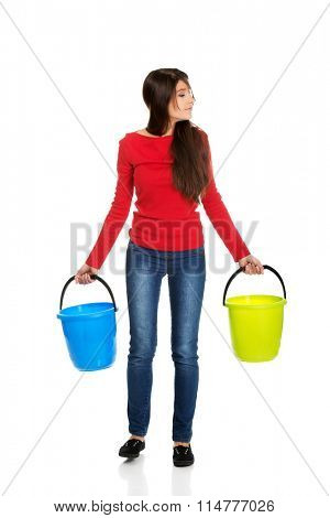 Woman holding empty plastic buckets.