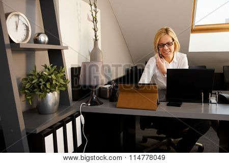 Portrait of businesswoman sitting at desk, working, talking on phone.