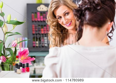 Woman getting manicure in nail parlor with file