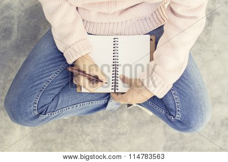 Girl With Blank Diary And Pen On Concrete Floor