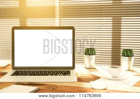Blank Laptop Screen On Wooden Table With Cup Of Coffee And Grass In The Bucket, Mock Up