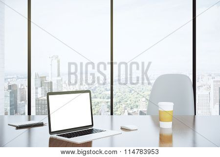 Blank Screen Of Laptop And Paper Cup On The Table With White Chair And City View From Big Window, Mo