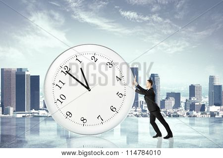 Stop Timing Concept With Businessman Pushing Big Clock At City Background