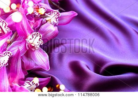 Beauty Elegant Violet Silk and Orchid flowers background with copyspace. Valentine's Day or Wedding background. Smooth Satin with orchids closeup