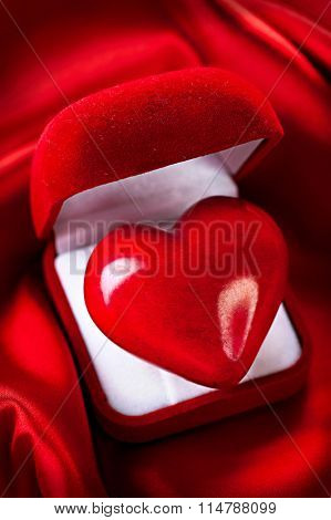 Valentine Heart in Gift box on Red Silk Background. Holiday background. Romantic St. Valentine's Day card design. Red velvet Gift Box with a heart on silk. Love