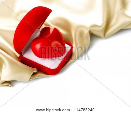 Valentine Heart in Gift box on Golden Silk border on white Background. Holiday background. Romantic St. Valentine's Day card design. Red velvet Gift Box with a heart on smooth satin. Love