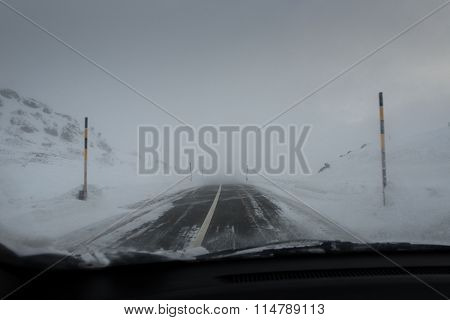 Driving car mountain road with snowstorm in the swiss alps