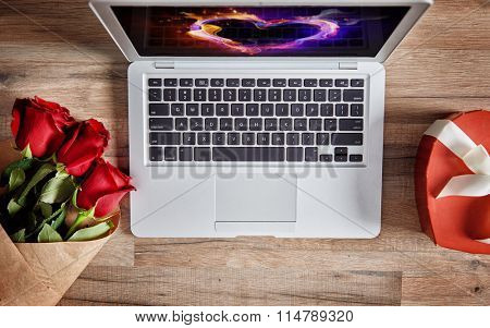 Bouquet of roses, gift box, laptop on wooden table. Top view. The concept of love and Valentine's day.