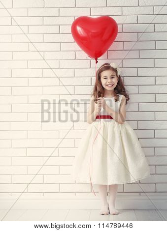 Sweet child girl with red heart. Happy little girl with red balloon at a blank brick wall. Wedding, Valentine concept.