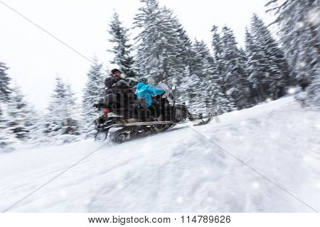 Snowmobile on winter forest road