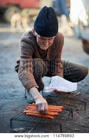 Senior Man Grilling Sausages