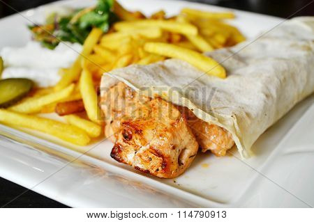 Big white plate with French fries, chicken meat in pitta bread, pickles, salad and sauce