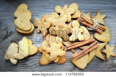 Gingerbread cookies in shapes of heart, star and man with cinnamon stick and ginger root