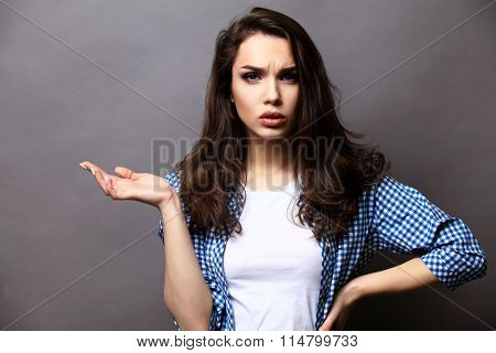 Smiling woman in gesture of asking over gray background.