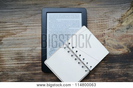 Black ereader with a small old notebook on wooden table