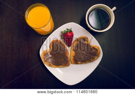Heartshaped pancakes covered with chocolate and strawberry, orange juice, cofee cup as seen from abo