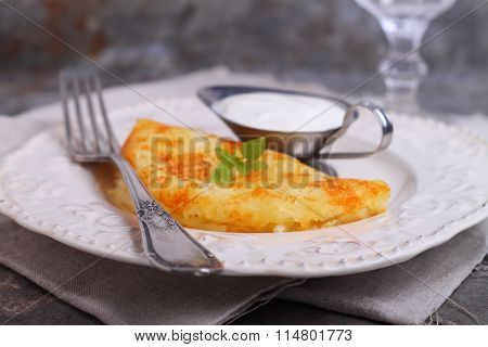 Potato Pancakes With Sour Cream In A White Plate