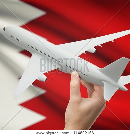 Airplane In Hand With Flag On Background - Bahrain