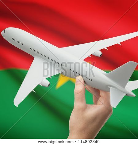 Airplane In Hand With Flag On Background - Burkina Faso