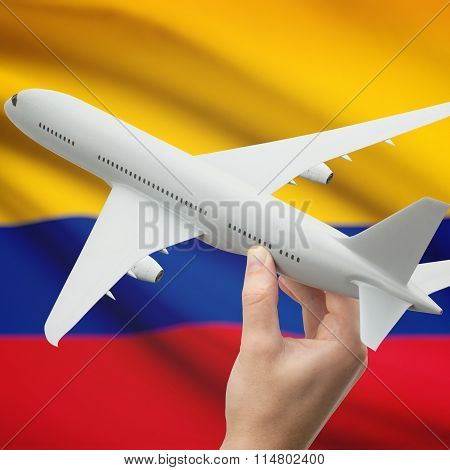 Airplane In Hand With Flag On Background - Colombia
