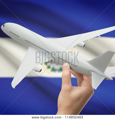 Airplane In Hand With Flag On Background - El Salvador