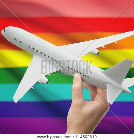 Airplane In Hand With Flag On Background - Lgbt People