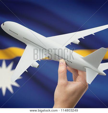 Airplane In Hand With Flag On Background - Nauru