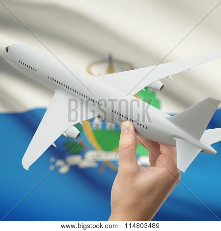 Airplane In Hand With Flag On Background - San Marino