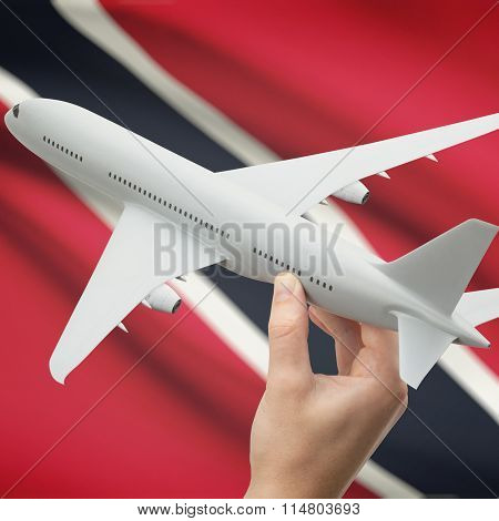 Airplane In Hand With Flag On Background - Trinidad And Tobago